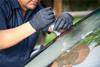 Pracownik uszczelnia przednią auto szybę